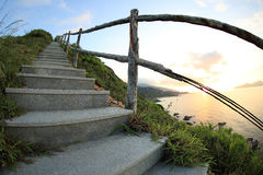 Seaside mountain stairs lead to sky at sunrise Royalty Free Stock Photography