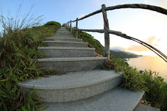 Seaside mountain stairs lead to sky at sunrise Royalty Free Stock Images