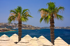 Seaside with palms. Two palms over restaurant roof and blue sea behind them Royalty Free Stock Images