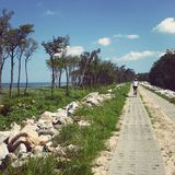 Seaside path. A seaside path with small figure of a woman cyclist Royalty Free Stock Photo