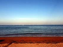 Sunny Seaside Scene with Sailing Boats on the Horizon. Seaside photograph with a sandy beach in the foreground and sailing boats, taking part in a boat race, in stock image