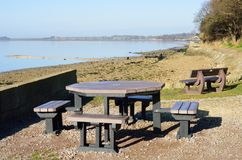 Seaside picnic tables by coast Royalty Free Stock Images
