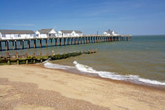Seaside Pier, England. Golden sandy beach and pier under a cloudless blue sky at a traditional English seaside resort. Southwold, Suffolk,  East Anglia, England Royalty Free Stock Photography