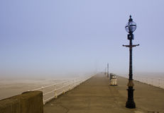 Seaside pier in fog. Whitby west pier, Yorkshire, England stock photography