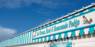 Seaside Pier Ice Cream and Candy. Bright colourful banner on an English seaside pier advertising ice cream, rock, candy cane  and homemade fudge. Paignton Royalty Free Stock Photography
