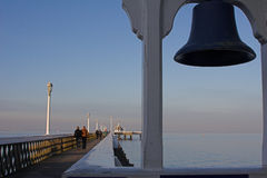 Seaside pier, with ships bell. Victorian seaside pier with ships bell in foreground Royalty Free Stock Photos