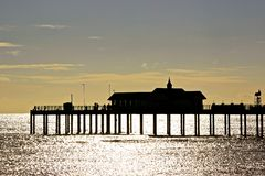 Seaside Pier in Silhouette. Southwold Seaside Pier in Silhouette with the low sun behind Stock Photo