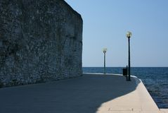 Seaside portwalk. Seaside port walk in Poreč (Parenzo), Croatia. Stone wall, shadow and two lamps Stock Photography