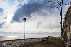 Seaside promenade benches and lamp-standards. Royalty Free Stock Images