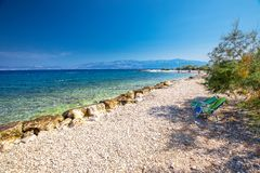 Seaside promenade on Brac island with palm trees and turquoise clear ocean water, Supetar, Brac, Croatia. Seaside promenade on Brac island with palm trees and royalty free stock photography