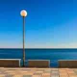 Mediterranean Seaside Promenade in Spain. Empty seaside promenade on the Mediterranean coast, overlooking calm blue sea on a sunny day. Malaga, Costa del Sol Royalty Free Stock Photos
