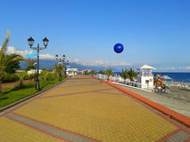 The seaside promenade at sunny day. The seaside promenade, Imeretinsky resort, Sochi, Russia. Sunny day, palm trees, blue sea and sky Stock Photo