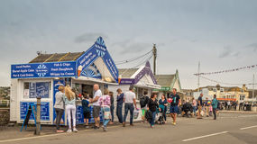 Seaside Refreshments. A small parade of refreshment kiosks situated along a seaside promenade. Numerous people including  families with children are out enjoying Royalty Free Stock Image