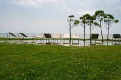 Seaside resort, chaise longue, sea, grass, trees Royalty Free Stock Image