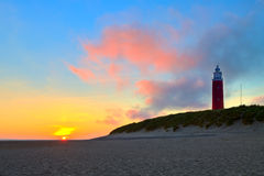 Seaside with sand dunes and lighthouse at sunset stock photography