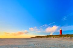 Seaside with sand dunes and lighthouse at sunset Royalty Free Stock Photo