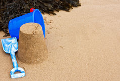 Seaside Sandcastle frame. Sandcastle, seaweed, bucket and spade on the beach Royalty Free Stock Photography