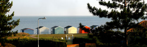 Seaside Sentinels. This photo shows a row of five beach huts standing to attention Stock Image