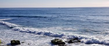 Seaside Series - Pacific Ocean Waves. Pacific Ocean waves crashing on sandstone beach at Wind and Sea Beach in La Jolla California. Surfers floating in the sea royalty free stock image