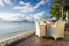 Seaside Table And Chairs. White table with chairs on decking, by the beach Stock Photo
