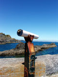 Seaside telescope. Rusty old seaside telescope at the seaside with rocky coast stock photography