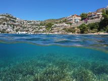 Seaside town Spain Costa Brava seagrass underwater. Seaside town in Spain on the Costa Brava and seagrass meadow underwater, split view above and below water Royalty Free Stock Image