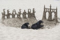 Sand castle with two dogs stock photography
