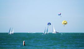 Seaside vacation. Sailboats and parchutes for seaside vacation fun Royalty Free Stock Photography