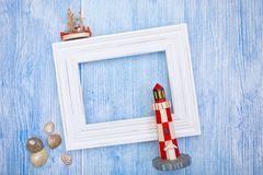 Seaside vacation background with copy space. Small fishing trawler, lighthouse, seashells and white picture frame as copy space on weathered blue wood Stock Photos