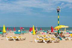 Seaside visitors relaxing in beach chairs at Dutch beach of Scheveningen royalty free stock photo