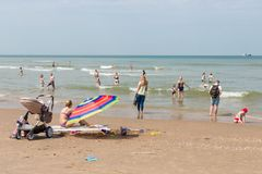 Seaside visitors relaxing at Dutch beach of Scheveningen stock photography