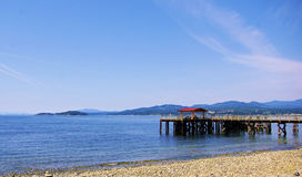 Seaside vista on spring day. Pier and sandy beach at seaside Royalty Free Stock Photos