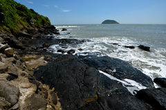 Seaside volcanic rock. Volcanic rocks on beach beside sea, with black color and featured texture Stock Images