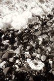 Seaside waves pebble. Seaside waves roll over pebbles on beach in monochrome stock photo