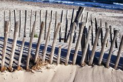 Seaside weathered wooden fences on sandy beach stock photos