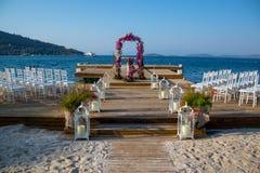 Seaside wedding flowers, white chairs white candlesticks stock photo