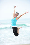 Seaside woman jumping Royalty Free Stock Photos