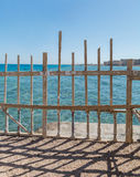 Seaside wooden fences against aqua sea and blue sky Royalty Free Stock Photos
