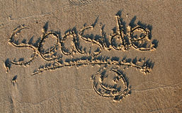 Seaside written in sand Stock Photos