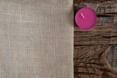 Season's贺卡与拷贝空间的设计观念 在粗糙的木背景的米黄布料与一个兰花紫色蜡烛 库存照片