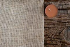 Season's贺卡与拷贝空间的设计观念 在粗糙的木背景的米黄布料与一个日落珊瑚蜡烛 免版税图库摄影