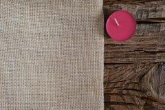 Season's贺卡与拷贝空间的设计观念 米黄布料,在粗糙的木背景的一个桑树紫色蜡烛 免版税库存图片