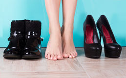 Season change concept. A woman chooses a ribbon or winter footwear Stock Images