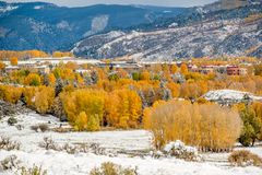 Season changing, first snow on roof. Season changing, first snow and autumn trees. Rocky Mountains, Colorado, USA Royalty Free Stock Images