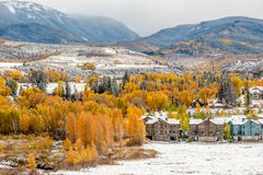 Season changing, first snow on roof. Season changing, first snow and autumn trees. Rocky Mountains, Colorado, USA Stock Photo