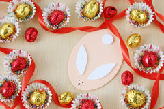 Season decoration: easter chocolate eggs frame with hand made bunny on wood background Royalty Free Stock Photography