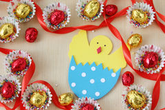 Season decoration: easter chocolate eggs frame with hand made hatched chicken in eggshell on wood background Royalty Free Stock Photo
