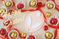 Season decoration, greeting card: easter chocolate eggs frame with hand made bunny on wood background Royalty Free Stock Image