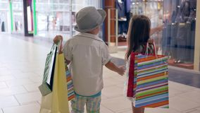 Season of discounts, small boy with girlfriend with packages after buy in stylish shops looking at store windows at. Shopping center on vacation stock footage