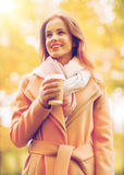 Happy young woman drinking coffee in autumn park. Season, hot drinks and people concept - beautiful happy young woman drinking coffee or tea from disposable Royalty Free Stock Photography
